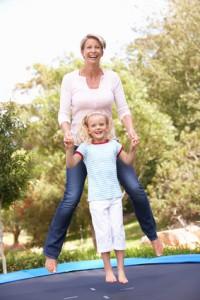 Mutter und Kind springen auf Trampolin